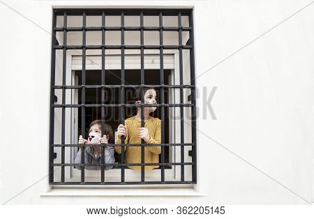 Two Children Look Sadly Outdoors Through Wrought-iron Window. Impact On Children Of Covid-19 Confine