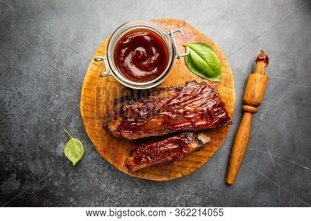 Delicious Bbq Baby-back Ribs With Tangy Sauce And A Basting Brush On Black Background, Top View