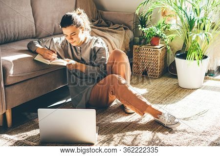 Young Beautiful Woman Works From Home. Sits On The Floor. Girl Uses A Laptop In A Sunny Room. Writes