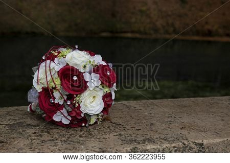 An Elegant Wedding Bouquet Of White And Red Roses Lies On A Stone Parapet On A Background Of A Mount