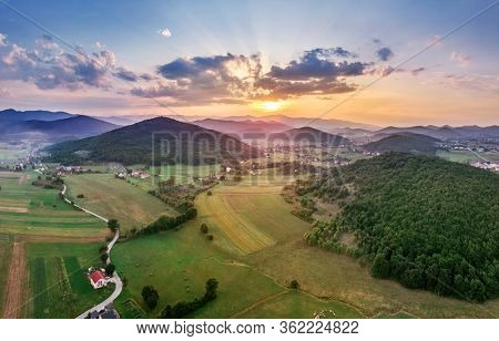 Beautiful sunset in mountains in Croatia. Bird's eye view panorama of amazing sky and the red sun lights shooting clouds over valley.
