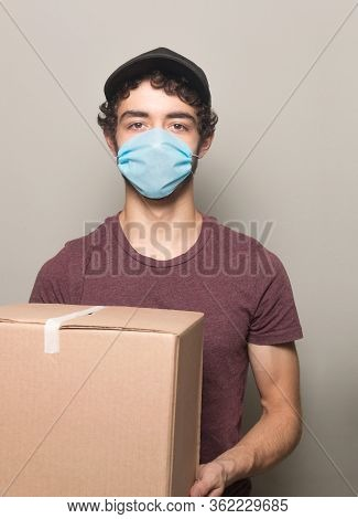 Delivery Young Men With Box  Wearing A Face Mask Vertical