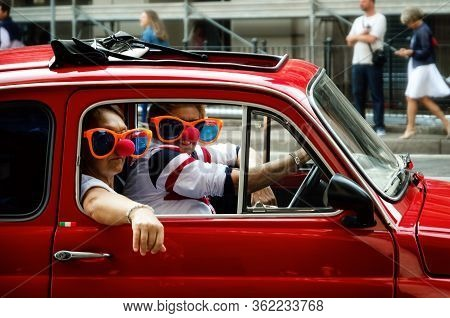 Turin, Italy - September 24, 2017 - Funny Looking Couple Driving An Old Red Fiat 500 During A Classi
