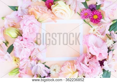 Flowers Composition. Frame Made Of Eustoma, Lilly And Daisy Flowers On Pink Background. Flat Lay, To