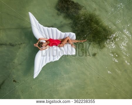 Beautiful And Sexy, Attractive Woman In Red Swimsuit Lays On Wing Shaped Inflatable Air Mattress Flo