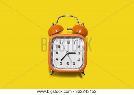 Vintage Style Orange Metal Alarm Clock With Bells Standing On The Yellow Background Isolated. Back T