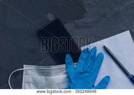 Medical Mask And Blue Nitrile Medical Gloves With A Smartphone For Remote Work On A Gray Heterogeneo