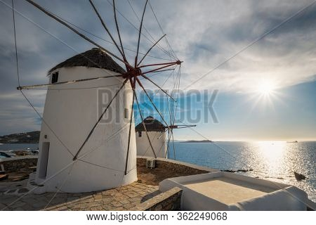 Scenic view of famous Mykonos town windmills. Traditional greek windmills on Mykonos island on sunset, Cyclades, Greece. Walking with steadycam.