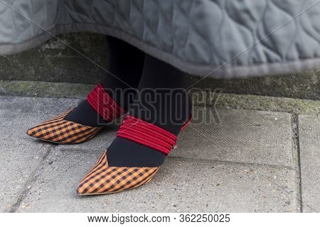 Fashionable People On The Street . Street Style. Ragged, Narrow-napkin Orange Shoes With Red Silk Co
