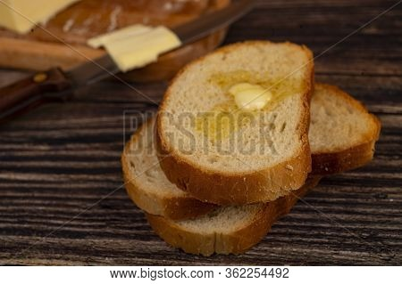 Fresh Wheat Toast With Butter And A Piece Of Butter In A Wooden Butter Dish On A Wooden Background.