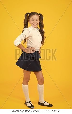 Exciting Back To School Style. Happy Small Girl Holding Long Ponytail Hair Style On Yellow Backgroun