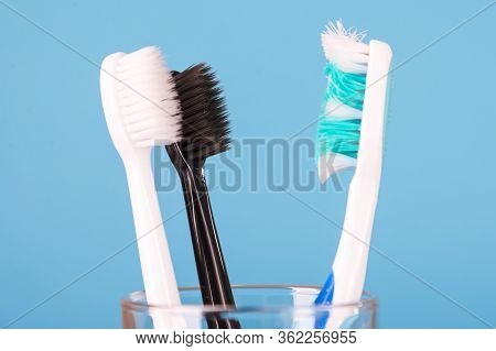 A New Toothbrush And An Old Damaged Toothbrush In A Glass From A Transparent Glass For Brushing Your