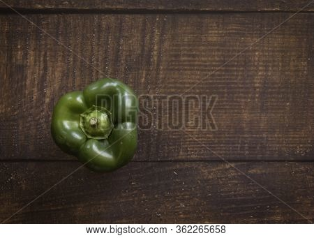 One Green Bell Pepper On A Wood Plank Background