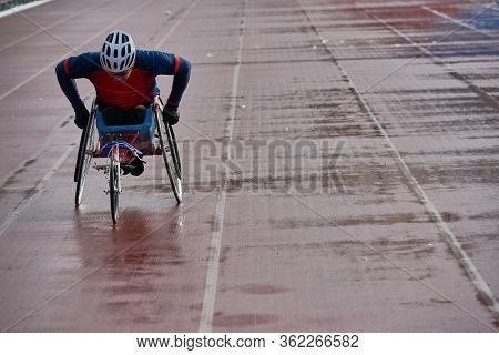 Wheelchair athletics. Strong-willed physically impaired male athlete training speed in racing chair at outdoor track and field stadium