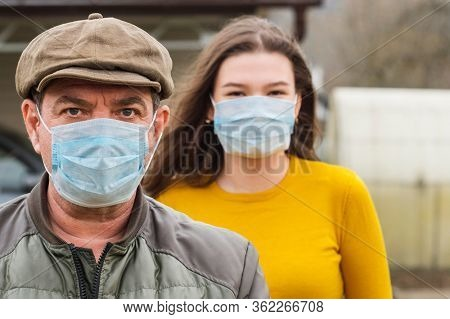 Adult man and young girl teenager in medical masks outdoors together