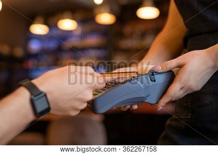 Contemporary young client holding plastic card over payment terminal in waitress hands while paying for drink or lunch in restaurant