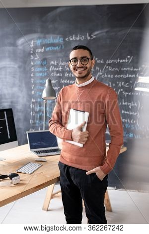 Portrait of cheerful young middle-eastern IT specialist in glasses standing with tablet in modern office, computer language script on blackboard