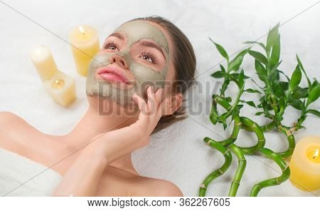 Spa Woman applying Facial green clay Mask. Beauty Treatments. Close-up portrait of beautiful girl lying down and applying facial mask in spa salon. Dayspa. Isolated on white background.
