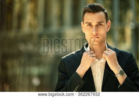 Business concept. Portrait of a goodlooking business man on a background of a big city. Men's beauty, fashion.
