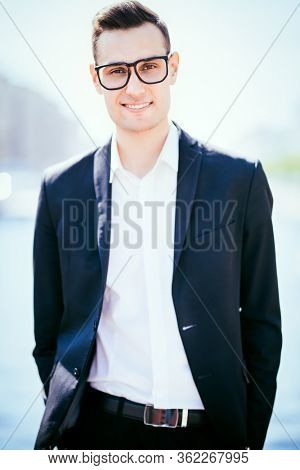 Business and vacation. Portrait of a happy goodlooking business man on a background of a big city. Men's beauty, fashion.