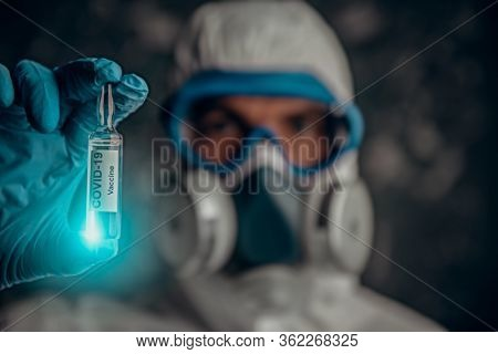 COVID-19 or 2019-nCoV. Doctor microbiologist scientist in a protective PPE suit shows the ampoule with a vaccine against coronavirus. Vaccination.