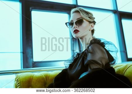 Fashionable young woman in black fur coat, elegant dress and sunglasses in interiors. Beauty, fashion. Optics and eyewear.