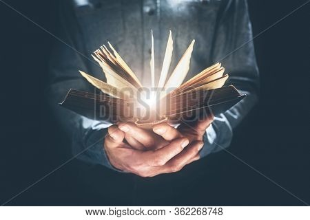 Man holding and reading the Holy Bible or a hard cover book concept for religion or study