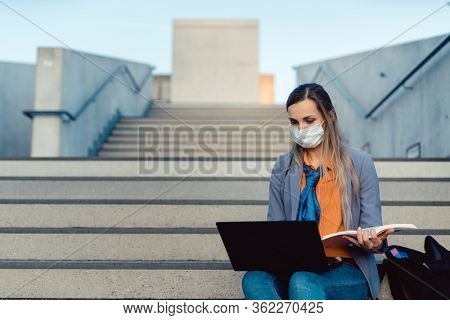 Student woman sitting on empty stairs of university campus working