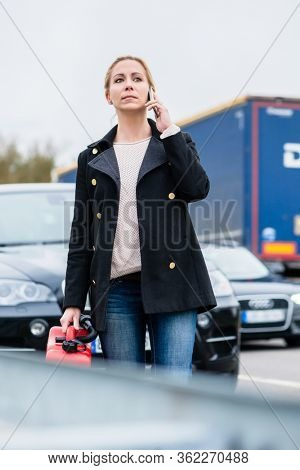 Woman out of gas car with spare canister in hand phoning for somebody to pick her up