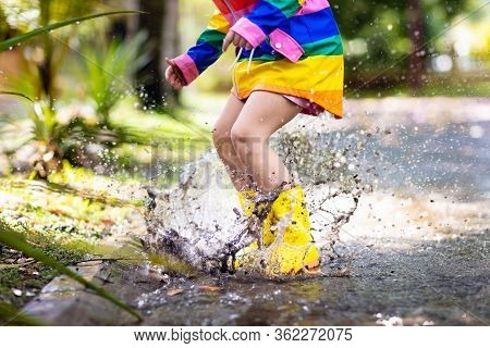 Kid Playing In The Rain In Autumn Park. Child Jumping In Muddy Puddle On Rainy Fall Day. Little Girl