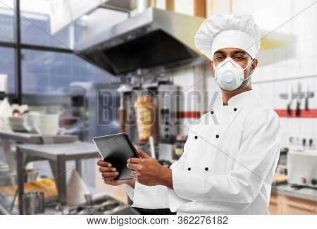 health protection, safety and pandemic concept - male indian chef in toque wearing face protective mask or respirator with tablet computer over kebab shop kitchen background