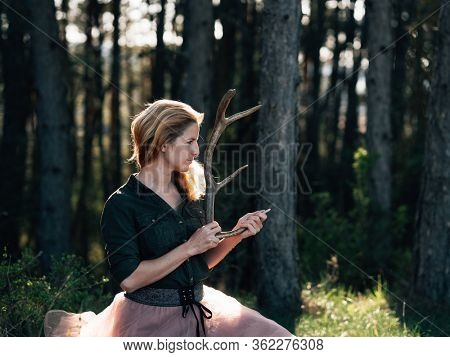 Young woman with antler in the forest