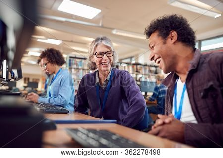 Teacher With Group Of Mature Adult Students In Class Working At Computers In College Library