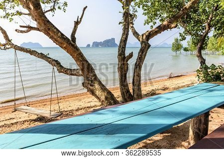 Covid-19 Lockdown. Empty Picnic Table & Wooden Swing Hangs From Tree On Deserted Beach On Ko Yao Noi