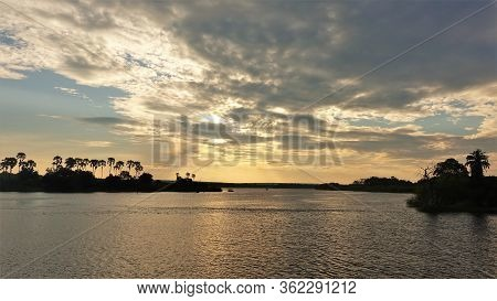 Sunset On The Zambezi River. The Expanse Of The River, Low Clouds, Tree Silhouettes And The Sun Sink