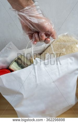 A Male Hand In A Glove Holds A White Bag With A Food Set. Dry Rations. Rice, Milk, Canned Food, Jam.