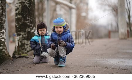 Two Little Funny Baby Brothers In Baby Caps Squatting On An Alley In The Park. Little Brother With C