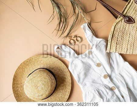 Women's Summer Straw Hat, Wicker Bag, White Sundress, Sunglasses And Jewelry On Beige Background. Co