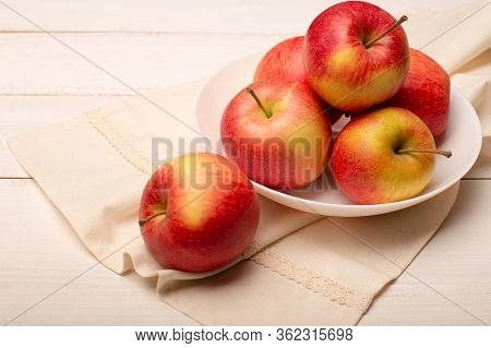 Close Up Of Ripe Red Apples In A Bowl On White Wooden Table, Selective Focus.