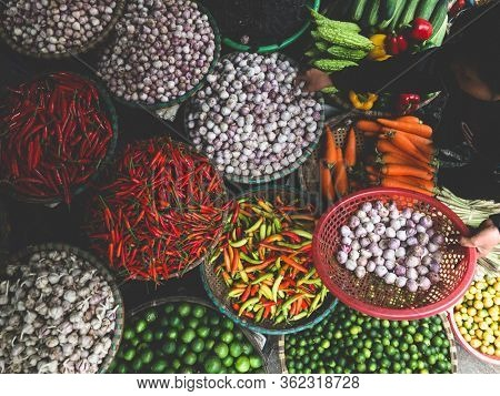 Hanoi, Vietnam, Febuary 1, 2020 - Fresh vegetables for sale at street food market in the old town.  Garlic, Lemon, Ananas, Onions, Peper, Red chillies, carots