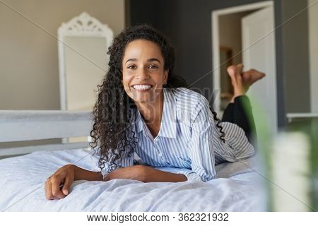 Cheerful young multiethnic woman looking at camera and smiling while lying on bed. Pretty casual mixed race woman lying on front on her bedroom. Portrait of beautiful african american girl resting.