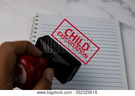Red Handle Rubber Stamper And Child Exploitation Text Isolated On White Background.