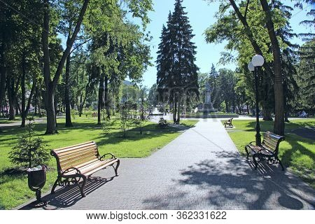 Beautiful City Park With Promenade Path Benches And Big Green Trees. City Park In Summer. Place For