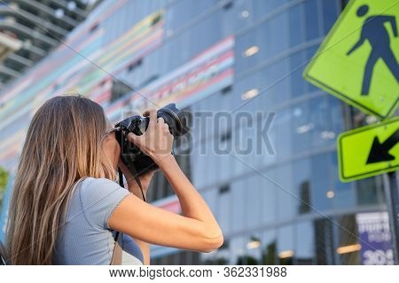 Female Photographing With Dslr Camera On The Street Photographing Building
