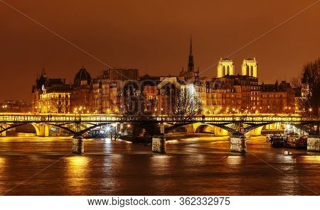 Bridge Of Arts On The Background Of The Island Of Cite At Night. Notre Damm Is Seen From Behind The