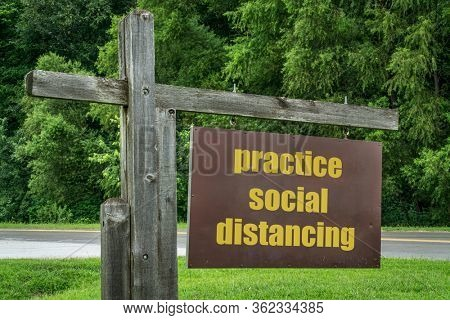 practice social distancing - park or trailhead sign against green trees, recreation during coronavirus covid-19 pandemic