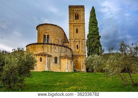Picturesque Tuscany. Ancient medieval magnificent abbey of San Antimo. Tall slender cypress adorns  the abbey. Autumn day. The concept of active, rural and photo tourism