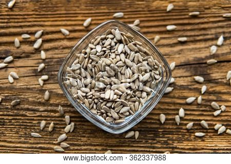 Sunflower Seeds In A Small Plate And Scattered Seed On The Wooden Vintage Table. Healthy Vegetarian