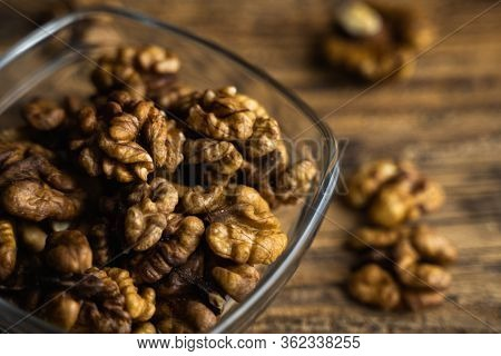 Walnut In A Smale Plate With Scattered Shelled Nuts Which Standing On A Wooden Vintage Table. Walnut