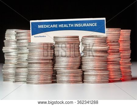 Many Stacks Of Old Silver Dimes With Medicare Health Insurance Card To Illustrate Budget Debt Fundin